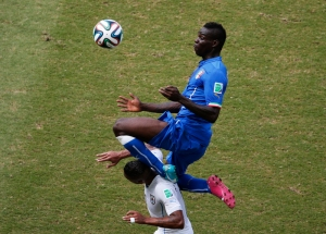 Italy's Mario Balotelli jumps on top of Uruguay's Alvaro Pereira during their 2014 World Cup Group D soccer match at the Dunas arena in Natal